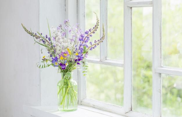 Wilde bloemen in vaas op witte vensterbank