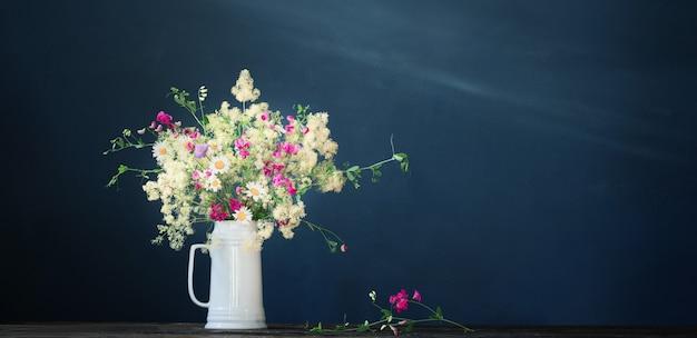 Wilde bloemen in witte kan op donkere achtergrond