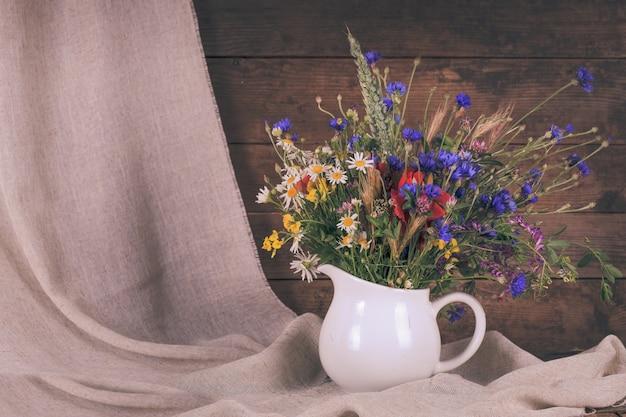 Wilde bloemen in witte keramische kan en kopjes op dienblad
