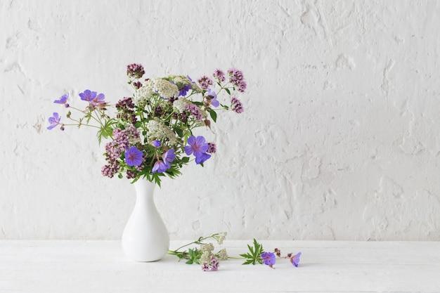 Wilde bloemen in witte vaas op witte achtergrond