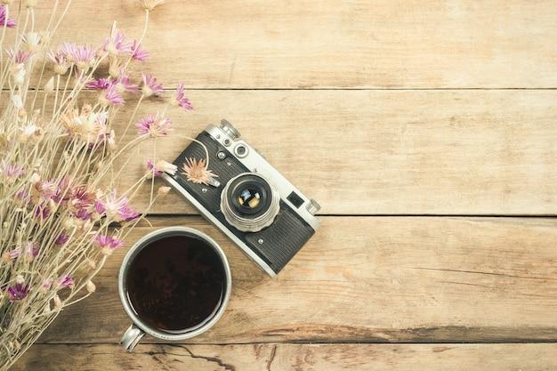 Wilde bloemen, metalen kopje thee, een kompas en andere attributen voor een wandeling op een houten oppervlak. concept van wandelen in de bergen of het bos, toerisme, tentrust, kamp. plat lag, bovenaanzicht.