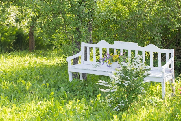 Wilde bloemen op witte houten bank in de zomertuin