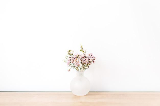 Wilde bloemen voor witte muur