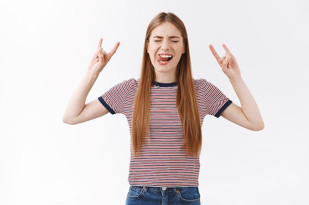 Wilde en zorgeloze knappe blanke studente in gestreept t-shirt gaat naar een geweldig feest, heeft plezier, toont geamuseerd lachende tong, sluit de ogen en maakt rock-n-roll-teken, heavy metal-muziek