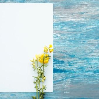 Wilde gele bloemen op leeg witboek over de geschilderde geweven achtergrond