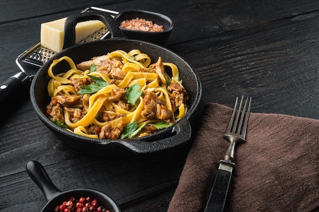 Wilde haas met groente in witte wijnsaus pasta tagliatelle of pappardelle set, in gietijzeren pan of pot, op zwarte houten tafel