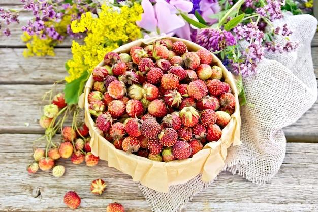 Wilde rijpe aardbeien in een schorsdoos met perkament, jute en wilde bloemen op de achtergrond van oude houten planken