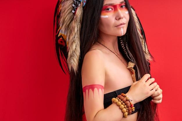 Wilde vrouw met kleurrijke make-up geïsoleerd in studio op rode muur, jonge vrouw draagt hoed gemaakt van veren op hoofd,