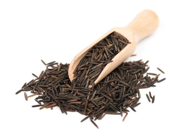 Wilde zwarte rijst in houten lepel die op wit wordt geïsoleerd