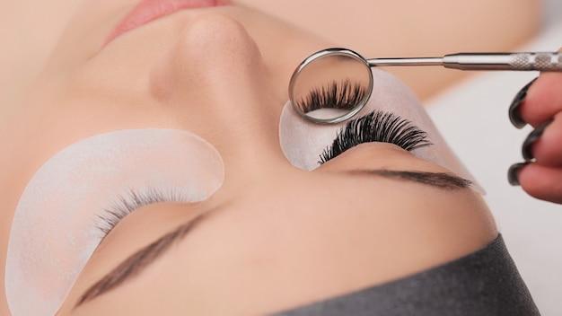 Wimper extensie procedure close-up. valse wimpers. make-up en schoonheidsconcept.