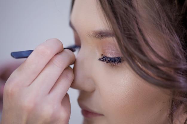 Wimper extensions, mooie make-up door een visagiste, een afbeelding voor een fotoshoot. close-up, make-upartiest met pincet die wimperextensions doet, een bos van kunstmatige wimpers