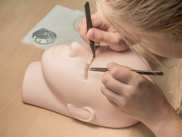 Wimperextensions trainen. werk aan het kleuren van wimpers op een mannequin.