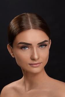 Wimpers extensions. valse wimpers. close-up van mooi jong vrouwelijk model met zachte vlotte huid en professionele gezichtsmake-up. portret van sexy meisje met lange nepwimpers en perfecte make-up.