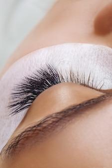 Wimperverlenging procedure vrouw oog met lange blauwe wimpers ombre effect close-up selectieve focus