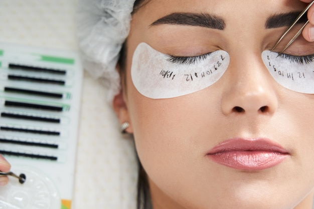 Wimperverlengingsprocedure close-up mooie vrouw met lange wimpers in een schoonheidssalon