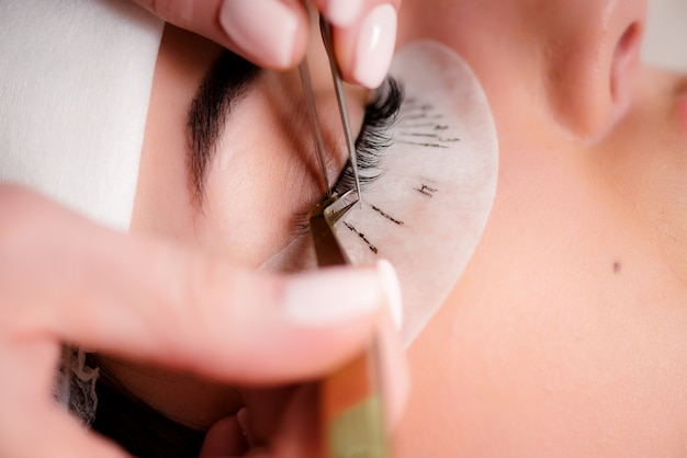 Wimperverlengingsprocedure. vrouw oog met lange wimpers. de wimpers, sluiten omhoog, macro, selectieve nadruk.