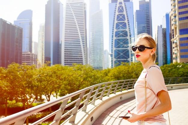 Wind blaast vrouwelijk haar terwijl ze op de brug staat voor mooie wolkenkrabbers van dubai