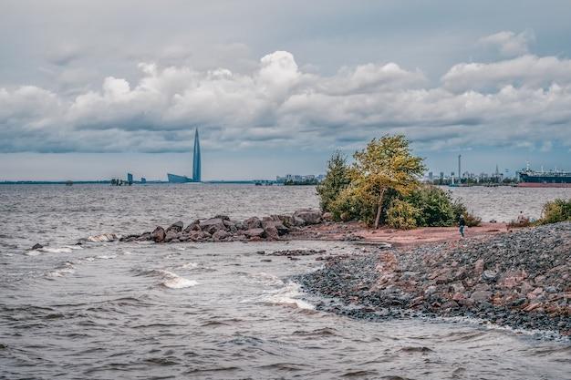 Winderige rotsachtige kust van de baai met rollende golven en wind. ten zuidwesten van sint-petersburg, uitzicht op de baai.