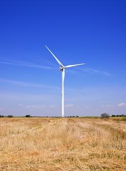 Windmolen in een veld tegen een blauwe hemel