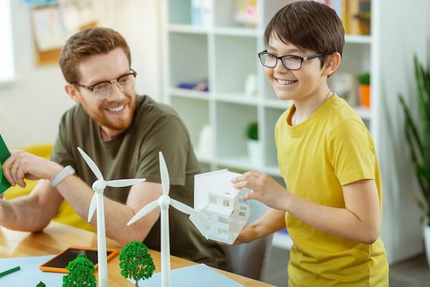 Windmolen infrastructuur. positieve kleine student die geïnteresseerd is in het leren van ecologie en gepresenteerde modellen vasthoudt