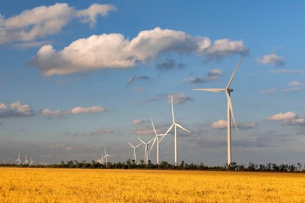 Windmolens op geel veld en blauwe hemelachtergrond. alternatieve energiebronnen.