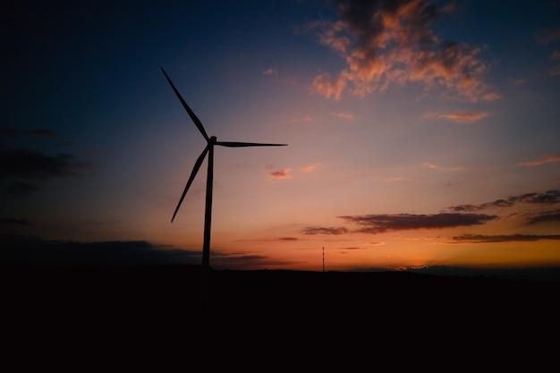 Windmolensilhouet bij de windturbinegenerator van de zonsonderganghemel