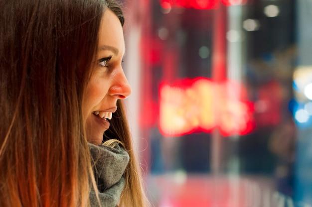 Window shopping, vrouw naar de winkel kijken. glimlachende vrouw die aan het winkelvenster wijst alvorens binnen te gaan. jonge vrouw kijkt naar de kleren in het winkelvenster