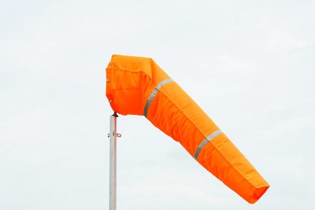 Windsock op bewolkte hemelachtergrond in winderig weer wijst op de lokale windrichting