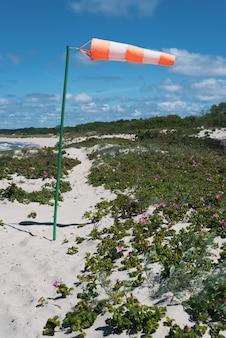Windsock op een achtergrond van heldere hemel aan de kust.