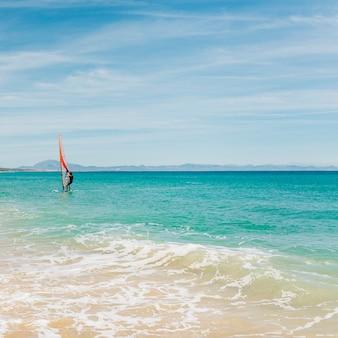 Windsurfer panorama silhouet tegen een vonkende blauwe zee.