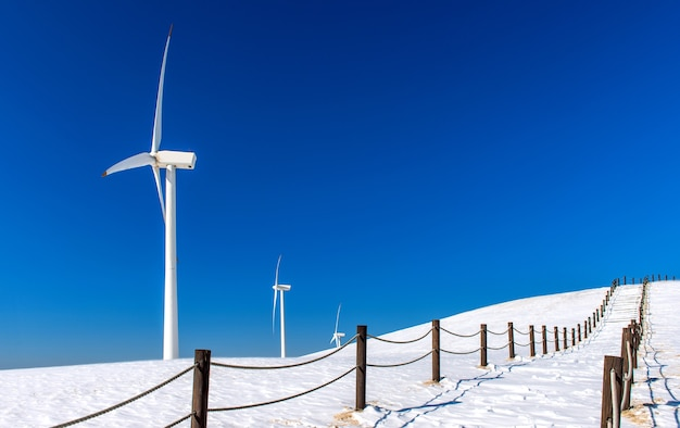 Windturbine en blauwe hemel in winterlandschap