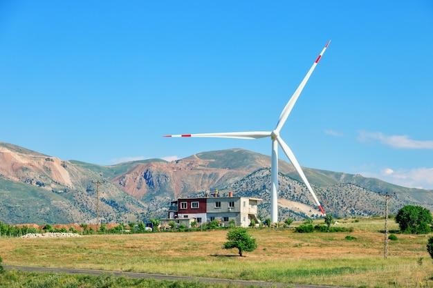 Windturbine en huis op heuvel onder blauwe hemel