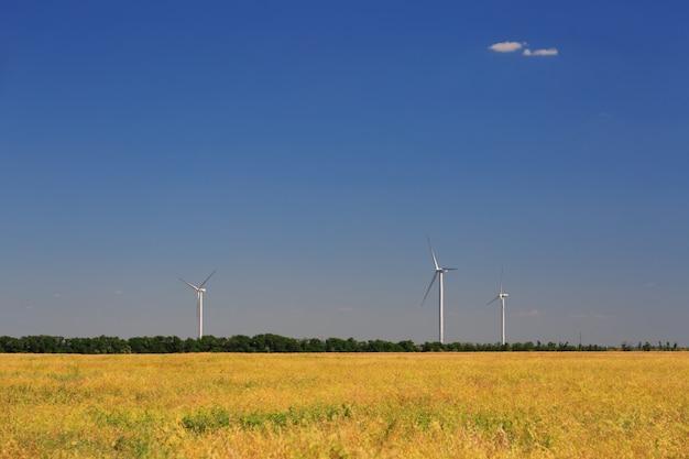 Windturbine, moderne windparken, windgeneratoren. geel veld op de voorgrond tegen een blauwe hemel