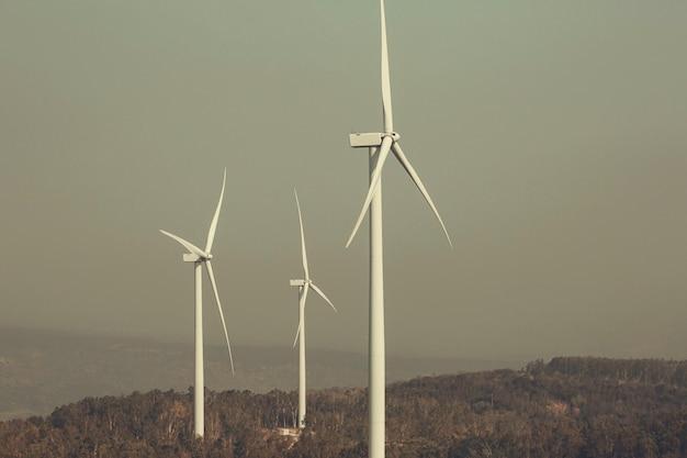 Windturbine op het bruine gras over berg de blauwe bewolkte