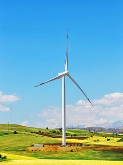Windturbine op heuvel tegen blauwe hemel
