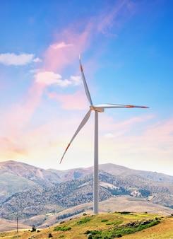 Windturbine op heuvel tegen de achtergrond van de dageraadhemel