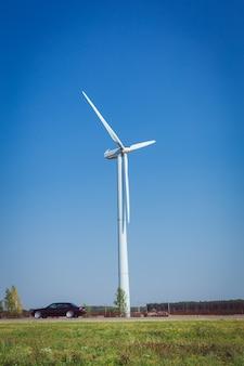 Windturbine opwekken van elektriciteit op het groene veld op zomerdag