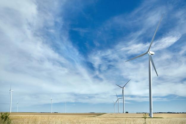 Windturbines in veld tegen bewolkte hemel