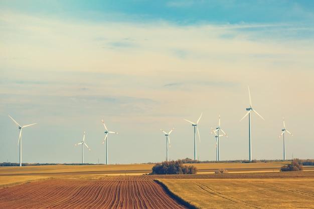 Windturbines op het gebied met blauwe hemel met wolken. afgezwakt