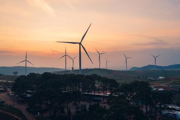 Windturbines van alternatieve energie met schoon en hernieuwbaar op heuvel in landbouwvelden 's avonds