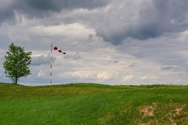 Windzak geblazen door de wind met een bewolkte hemel, eenzame boom en groen gazon