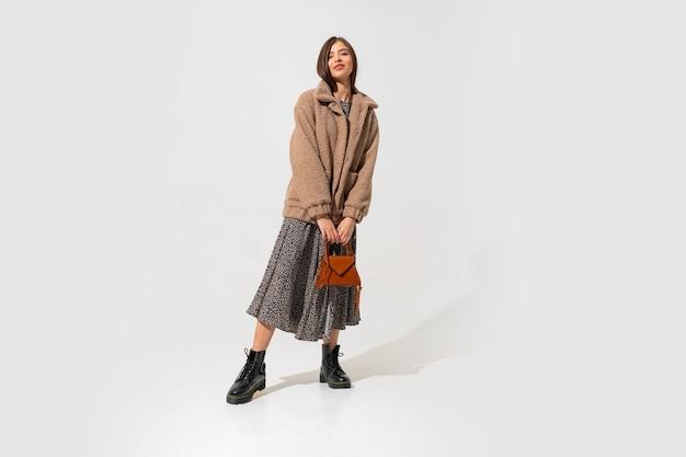 Winer fashion look. stijlvol donkerbruin model in beige bontjas en. volledige lengte.