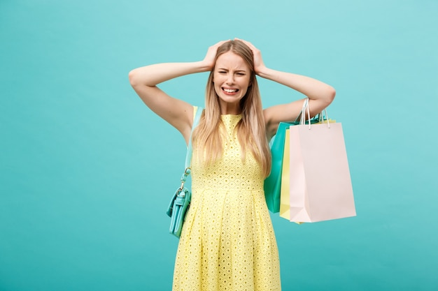 Winkel- en verkoopconcept: mooie ongelukkige jonge vrouw in gele elegante jurk met boodschappentas.