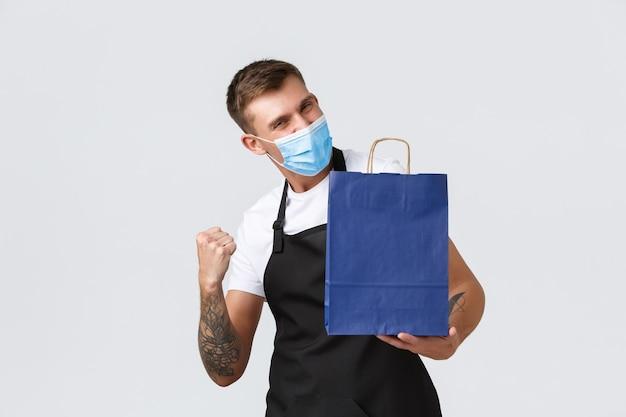 Winkel, winkelen tijdens covid-19 en concept voor sociale afstand. enthousiaste knappe verkoper die werkt tijdens de pandemie van het coronavirus in de winkel, vuistpomp als eco-tas met aankoop