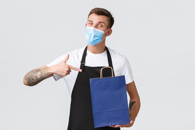 Winkel, winkelen tijdens covid-19 en concept voor sociale afstand. vriendelijke knappe verkoper in zwarte schort en medisch masker wijzende vinger naar eco-tas, witte achtergrond