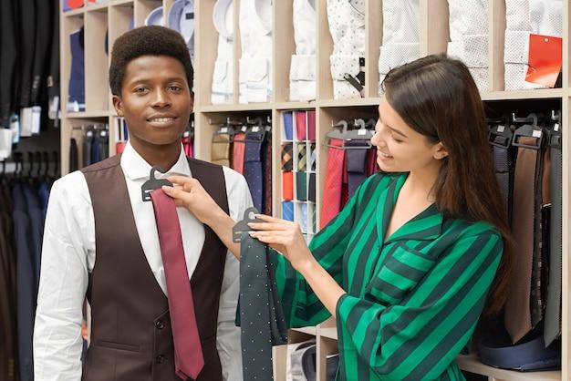 Winkeladviseur die stropdas voor cliënt in boutique proberen.