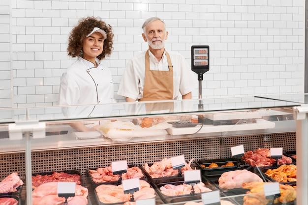 Winkelarbeiders poseren achter de toonbank.