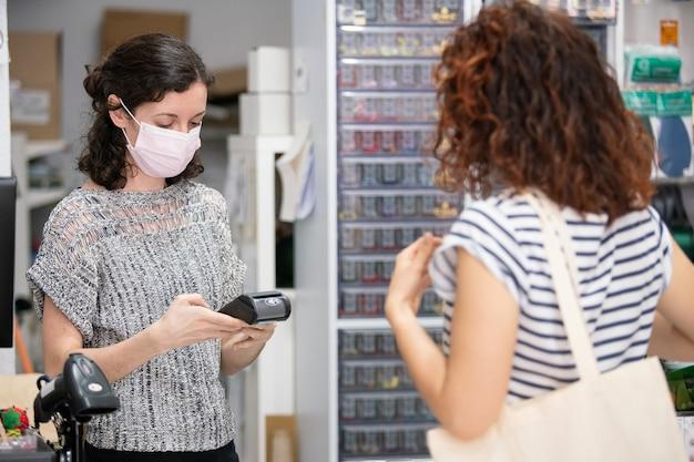 Winkelbediende aan de balie met een beschermend gezichtsmasker.
