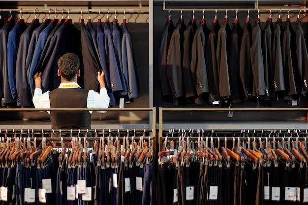Winkelbediende controleert jassen op hanger in herenkledingwinkel, uitzicht vanaf de achterkant