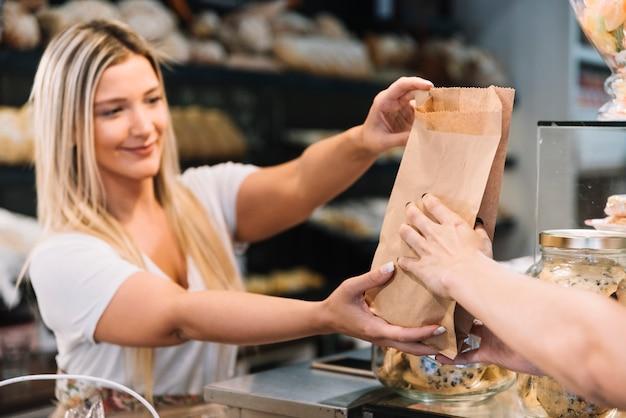 Winkelbediende die croissantzak geeft